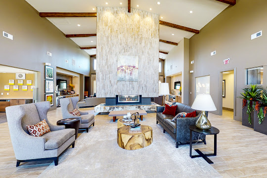 Clubhouse with light flooring, stone fireplace, and seating