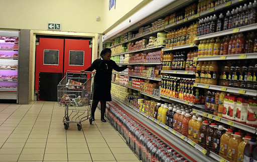 An eye on prices: A shopper makes her selection at a grocery store in Joburg. The Reserve Bank, keeping the repo rate unchanged for now, has noted that the inflation outlook faces several risks. Picture: REUTERS
