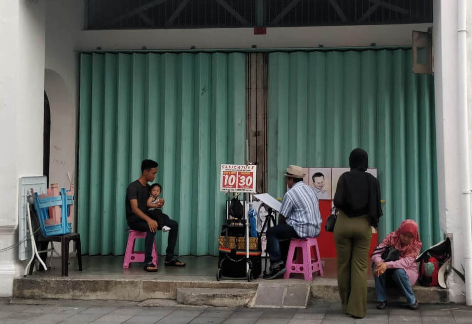 artist+making+sketches+penang+streets+georgetown++malaysia