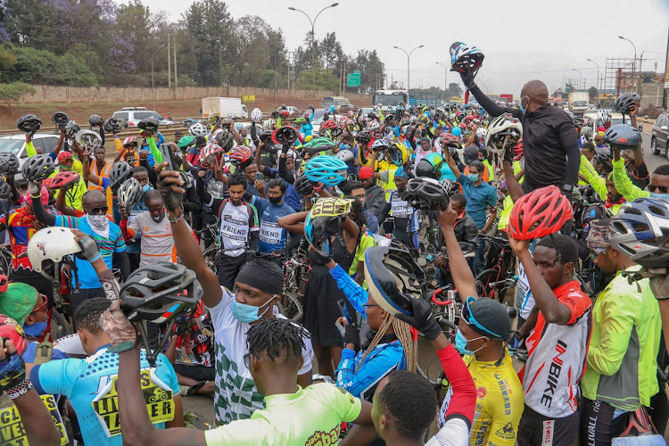 A crowd of cyclist raise their helmets in respect of one of their own Caleb Omwoyo died while cycling home.