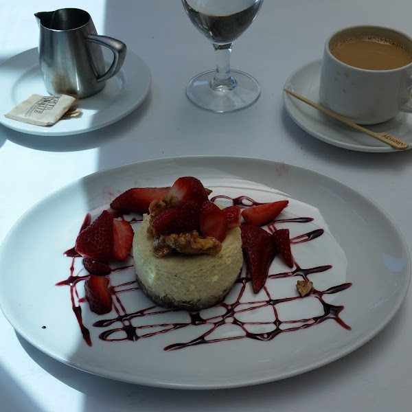 Awesome Chevre cheesecake with port-marinated strawberries and a buttery walnut crust, garnished with strawberry sauce and candied walnuts! So good! Don't let the size fool you. It is very rich.