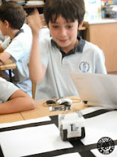 Photo: Kid happily programming the Infante Robot