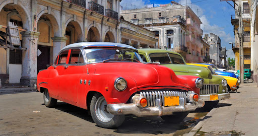 Cuba-Colorful-Cars-Angled-Parked_01.jpg - Vintage cars line a street  in Cuba.