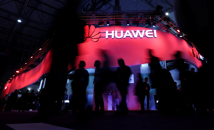Visitors walk past Huawei's booth.