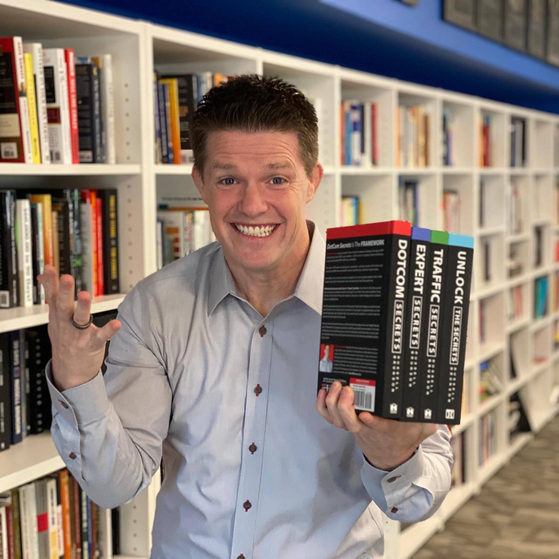 Russell Brunson holding four of his award-winning books