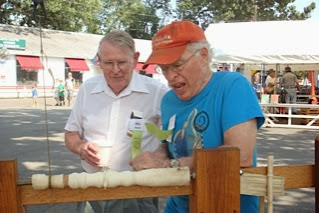 Photo: Phil Brown gives the pole lathe a try with Russ Iler kibitzing