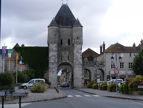 """Photo: The town entrance is through the Porte de Samois, one of the two basically identical gates which served as the only entrances to the town, at opposite ends of la rue Grande (basically, """"Main Street""""). The medieval ramparts which circled the town between the gates are now gone. The information plaque at the tower notes that one of the two circular turrets contained the staircase for the tower, while the other served as a surveillance point. The details of the construction, and the absence of a drawbridge, indicate that the tower was raised at the end of the 12th century."""