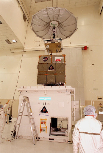 The Mars Climate Orbiter is lifted clear of the top of its container in the Spacecraft Assembly and Encapsulation Facility 2 SAEF 2.