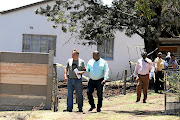 Former Kaizer Chiefs striker Mike Mangena, middle, after  a drug laboratory was found on his property in  Randfontein, West Rand.