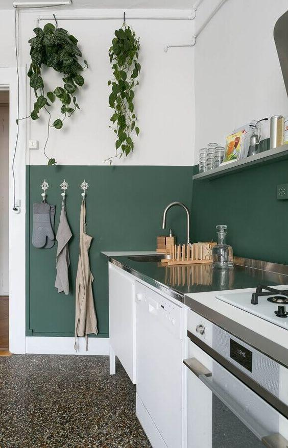 Cozinha com técnica de pintura meia parede verde e branca.