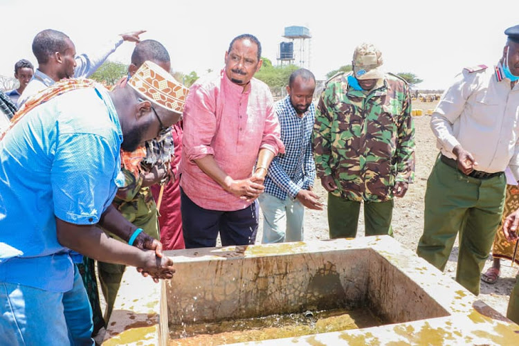 Wajir East MP Rashid Kassim [C] with other officials from the government and the WTS wash their hands at one of the cattle troughs