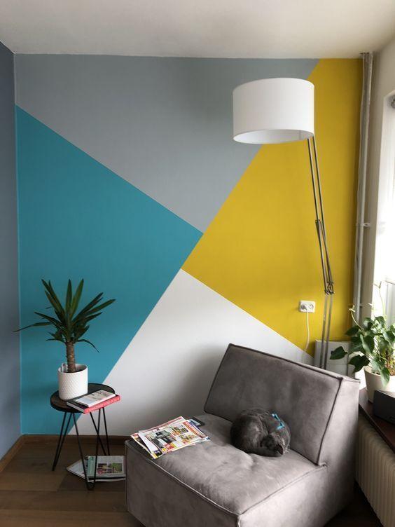 Sala de estar com parede principal com pintura geométrica nas cores azul, amarelo e branco e demais paredes cinza