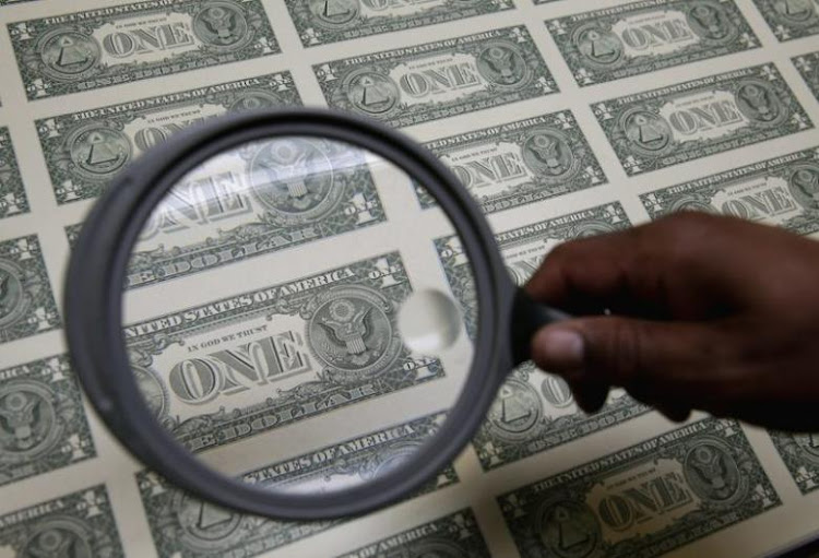 United States one dollar bills are inspected under a magnifying glass during production. Picture: REUTERS
