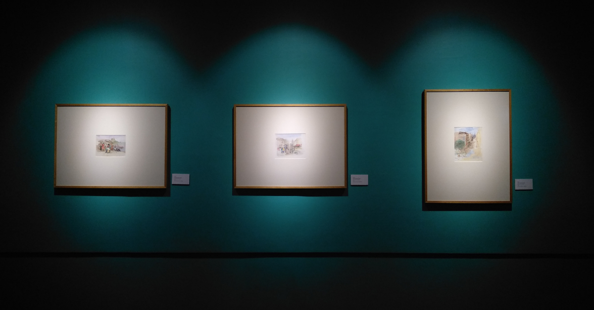 Three paintings hanging in a museum