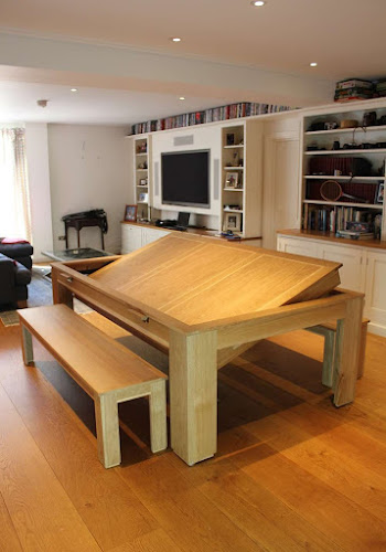 the light wooden spartanrollover dining table on a wooden floor in a lounge area