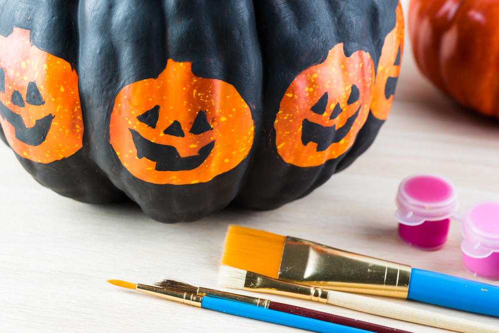 a painted pumpkin and paint supplies