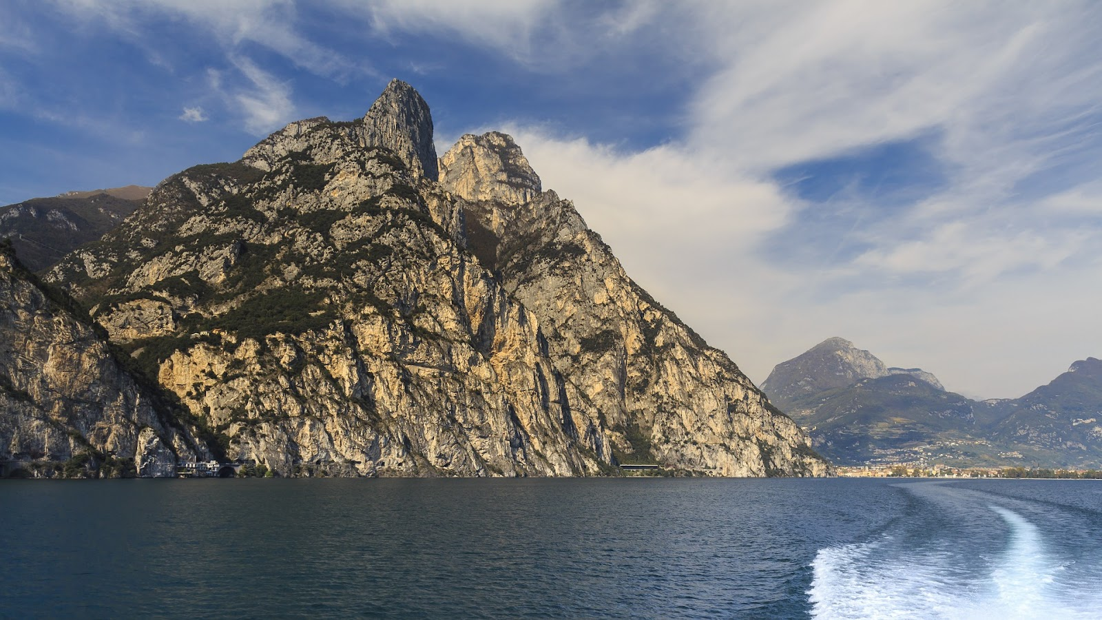 beautiful natural beauty near garda lake. Limone Sul Garda, small town in northern part of lago di garda. Large rocky hill seen from the lake's surface, trail from boat on the lake and clouds in distance.