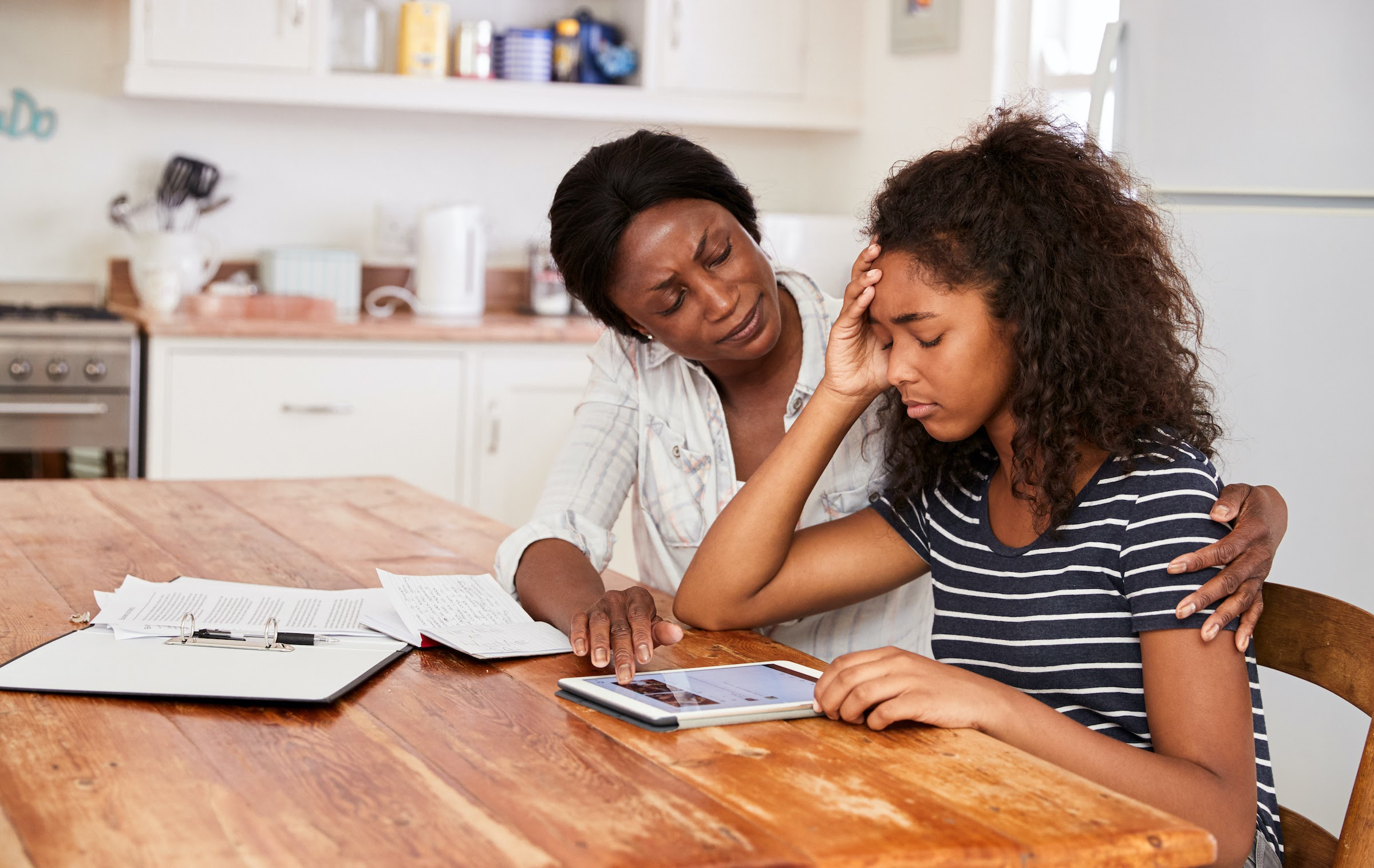 Mother helping frustrated daughter with schoolwork
