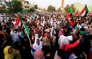Sudanese people chant slogans and wave their national flags as they celebrate, after Sudan's ruling military council and a coalition of opposition and protest groups reached an agreement to share power during a transition period leading to elections, along the streets of Khartoum, Sudan, July 5, 2019.