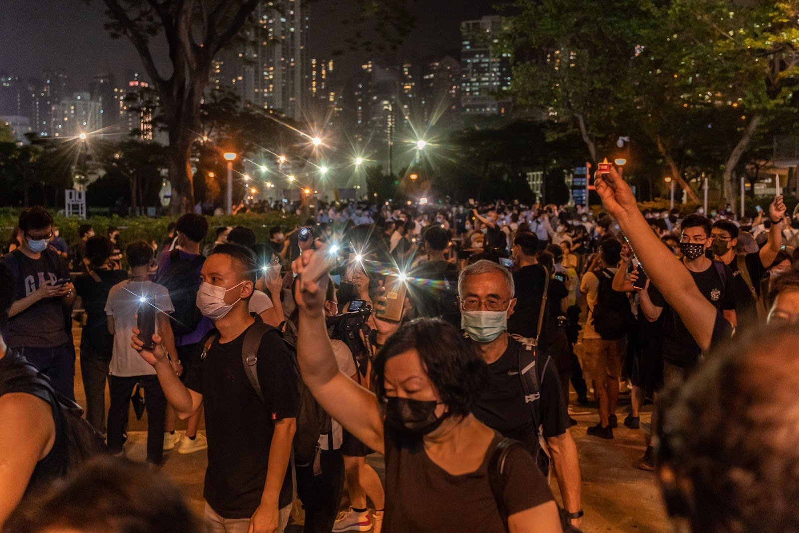 People hold up their phones with the light as they walk near Victoria Park after police closed the venue where Hong Kong people traditionally gather annually to mourn the victims of the Chinese Communist Party's 1989 Tiananmen Square Massacre in the Causeway Bay district on June 4, 2021 in Hong Kong.