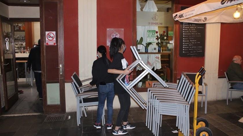 Trabajadores recogiendo las mesas de un establecimiento hostelero