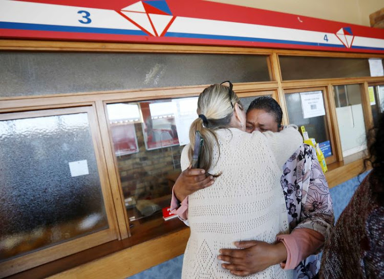 Women embrace as they mourn the death of UCT student Uyinene Mrwetyana at the post office in Cape Town where she was killed.