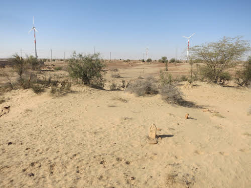 India. Rajasthan Thar Desert Camel Trek. Windmills from the army & old tomb stone.