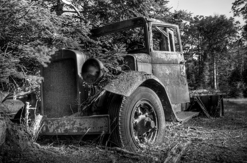"""Photo: I took this shot a few months ago at the old abandoned saw mill on Bois Blanc Island, Michigan.  I've been coming here since I was a little kid, and have always been fascinated with this old truck.. How long has it been here? What's the story of the men that used to drive it? Why did they leave it? Whatever the answers are, I agree with +Trey Ratcliff 's quote, """"When old trucks go to die, their final drivers seem to park them in a spot that will be perfect for photography some day. That's kind of them."""" One of my first experiments with black and white HDR"""