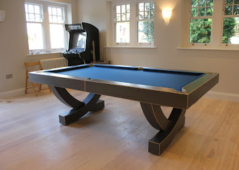 The arc pool table on wooden flooring with an arcade machine behind it