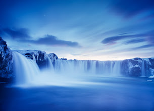 Photo: Godafoss, Iceland  One of the most photographed places in Iceland looks and sounds magnificent during the winter months. Snow and icicles make the waterfall feel even more surreal and ancient, like from a world billion years before us.  We spent one evening there trying to find the best angle to capture its mood. I'm choosing the very last photograph I made during the session, well after sunset. The film (Fuji Velvia 50) did what I expected it to do - shifted hues towards cool blues that I believed could have suited the scenery the best.  Enjoy!