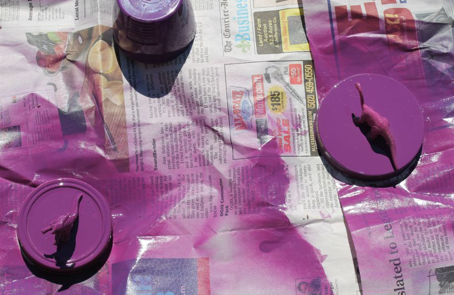 Spray paint the lids and dinosaurs with spray paint in your color of choice