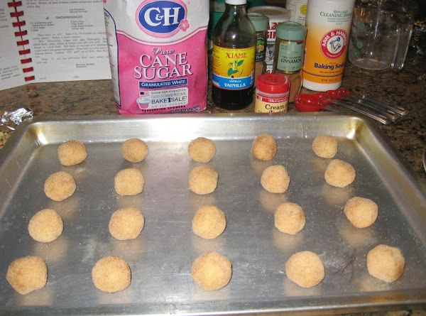 Using a tablespoon, scoop out dough and roll into a ball, roll in the...