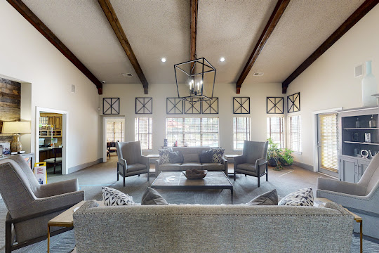 Community clubhouse with lounge seating, large windows, and a modern hanging light fixture