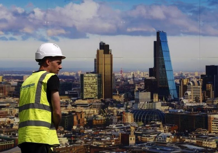 A worker walks past a picture of the London skyline outside the sales office of a property development in central London. Picture: REUTERS