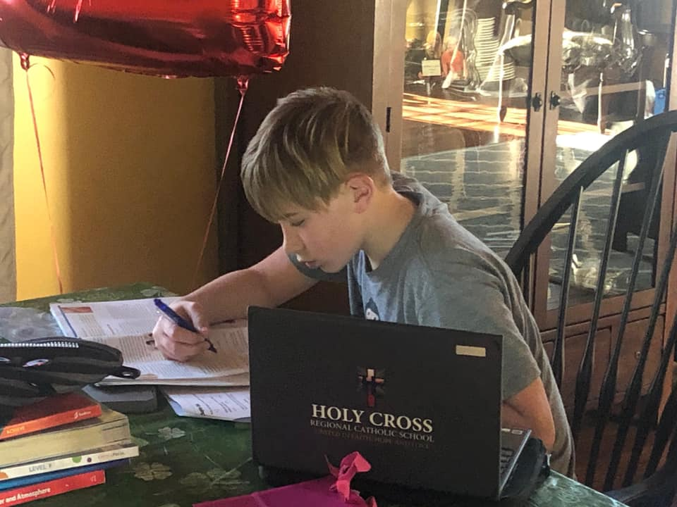 Holy Cross student does schoolwork with school-supplied Chromebook nearby.