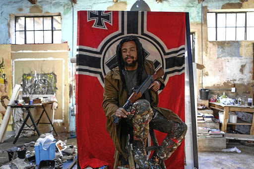 Artist Ayanda Mabulu strikes a carefully arranged pose in front of the war flag of the Third Reich at Victoria Yards studio in Lorentzville, Johannesburg.
