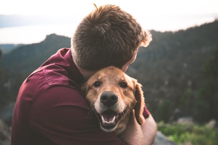 Homem abraçando seu cachorro.