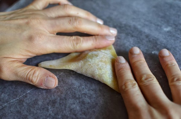 Using your index fingers, seal the edges of the wrapper on either side of...