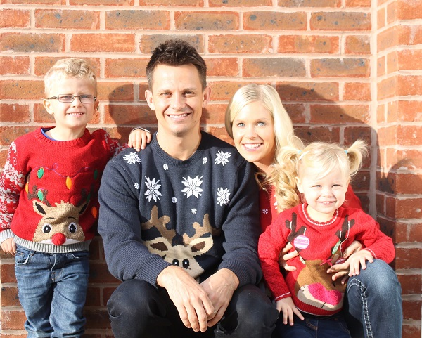 Two children and parents outside in reindeer jumpers