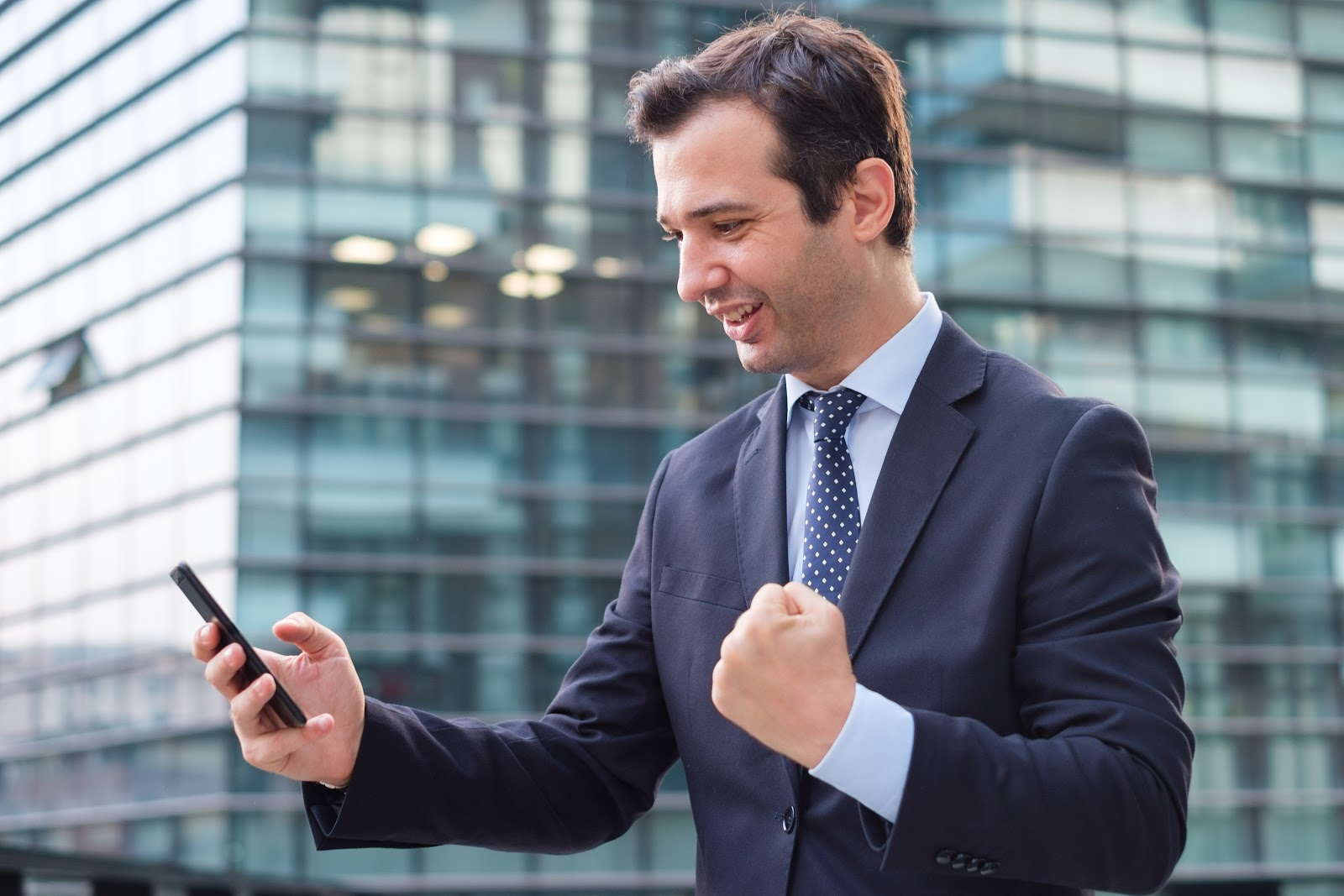 Man in a business suit holding his phone.