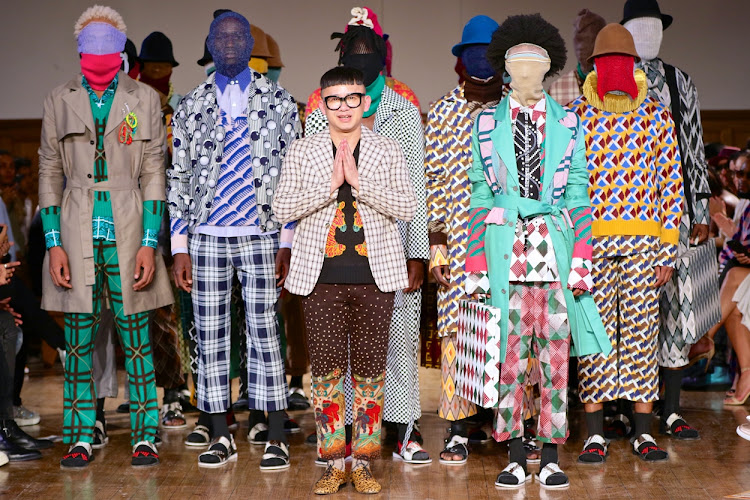 Chu Suwannapha flanked by 'faceless' models wearing his creations at SA Menswear Week in Cape Town.