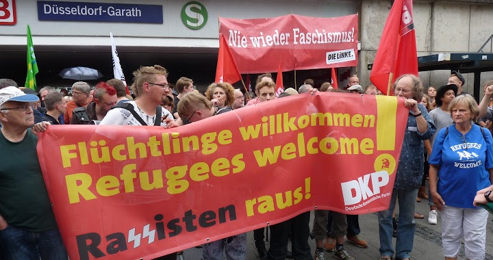 Demonstranten mit Transparent «Flüchtlinge willkommen…».