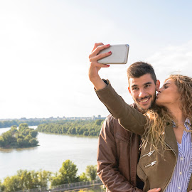 Happy young couple taking selfie photos near the river by Vera Arsic - People Couples ( young women, romance, two people, friendship, heterosexual couple, city life, togetherness, young adult, social networking, river bank, kissing, selfie, model, connection, communication, smiling, attractive, smart phone, telephone, lovers, lifestyles, girlfriend, enjoyment, color image, adult, photography, city, boyfriend, affectionate, modern, romantic, happiness, joy, dating, flirting, nature, carefree, sexy, intimate, young men, technology, people, love emotion, young couple, outdoors, bonding, couple relationship, fun, fashion, laughing )
