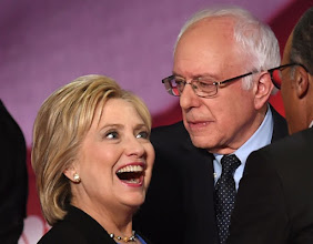 Photo: Democratic presidential candidates Hillary Clinton (L) and Bernie Sanders (R) confer during the NBC News -YouTube Democratic Candidates Debate on January 17, 2016 at the Gaillard Center in Charleston, South Carolina. / AFP / TIMOTHY A. CLARY        (Photo credit should read TIMOTHY A. CLARY/AFP/Getty Images)