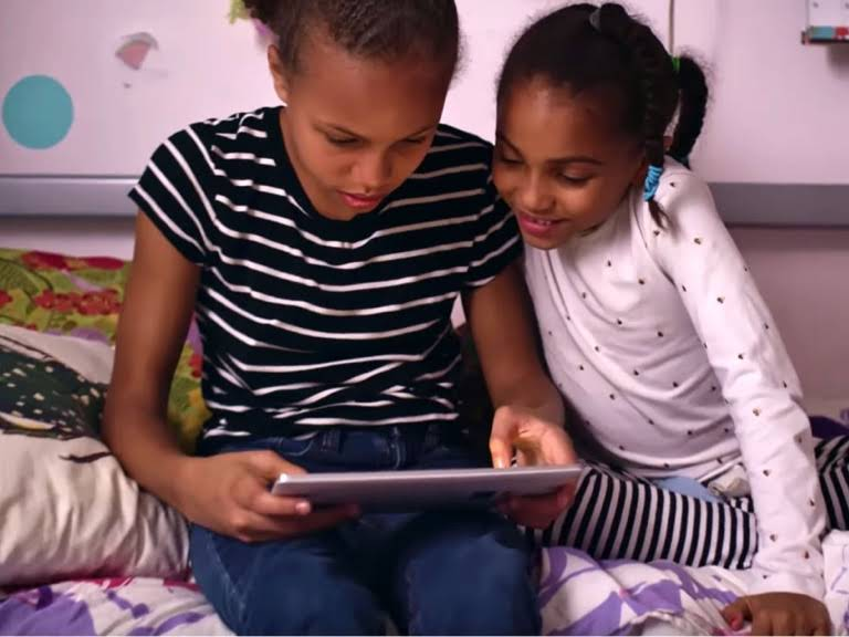 An older sister shares her Chromebook tablet with her younger sister.