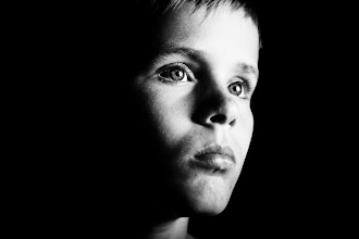 Photo: Troubled and thoughtful young boy alone in the dark
