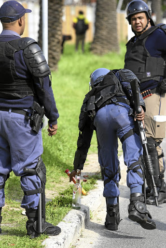 TOOLS OF DESTRUCTION: Riot police confiscate a petrol bomb and a flare left behind by protesters in Hout Bay.