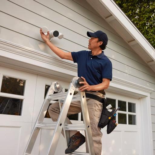 Un professionnel aide un client à installer une NestCam avec projecteur sur sa maison.
