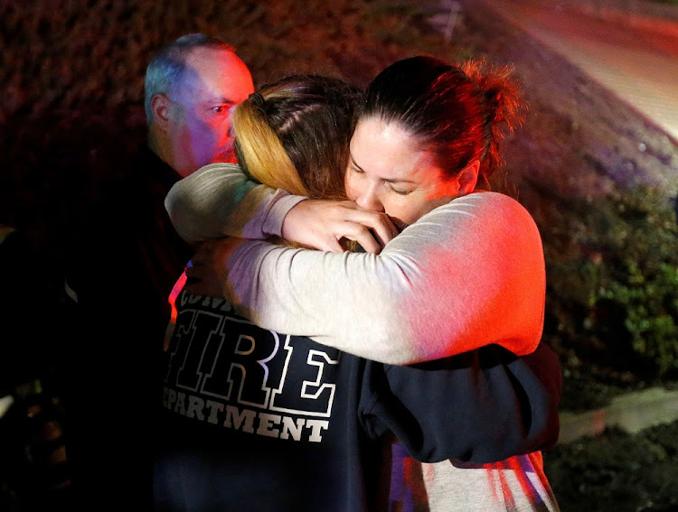 People comfort each other after a mass shooting at a bar in Thousand Oaks, California, the US, November 8 2018. Picture: REUTERS/RINGO GHIU
