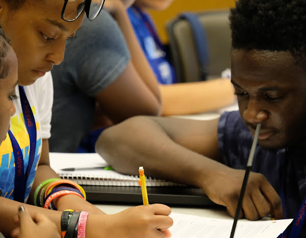 Photo of three students of color writing in a notebook